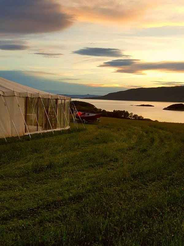Traditional marquee with full length clear walls and a wooden floor overlooking a loch in the Scottish Highlands