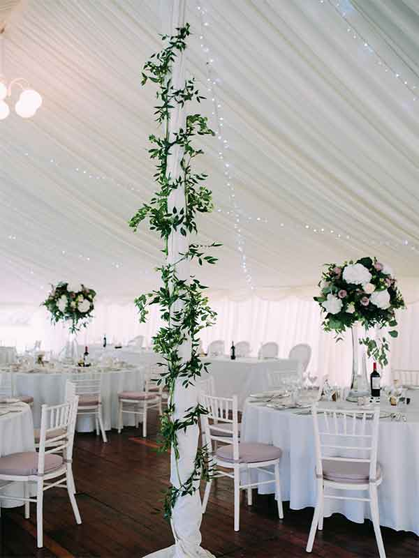 Centerpoles with floral decoration and matching table flowers in a wedding marquee hire in Scotland