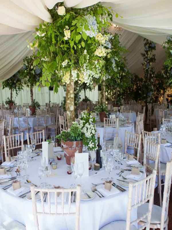 interior decor in small garden marquee with floral decorated centre poles