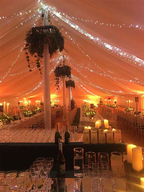 Four rows of tables in a New Century marquee hire for a wedding with center-poles decorated and lighting