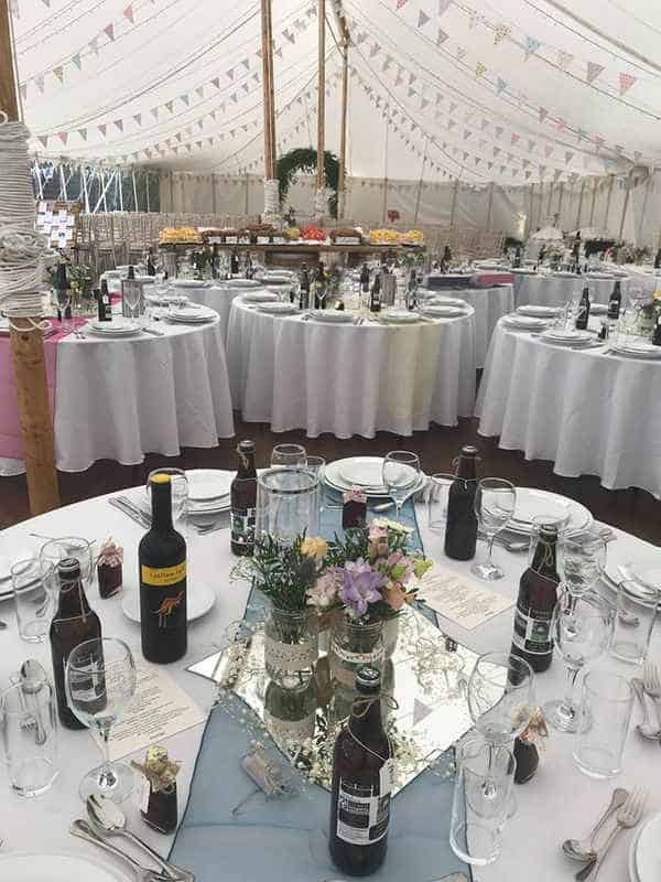 interior of marquee hire tent with tables set for wedding meal