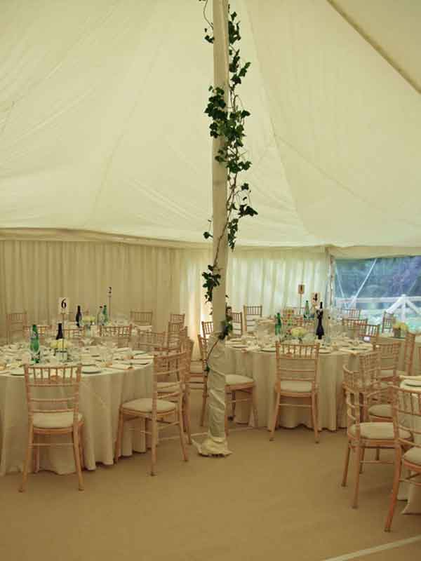 Marquee hire borders decorated marquee with floral centerpole