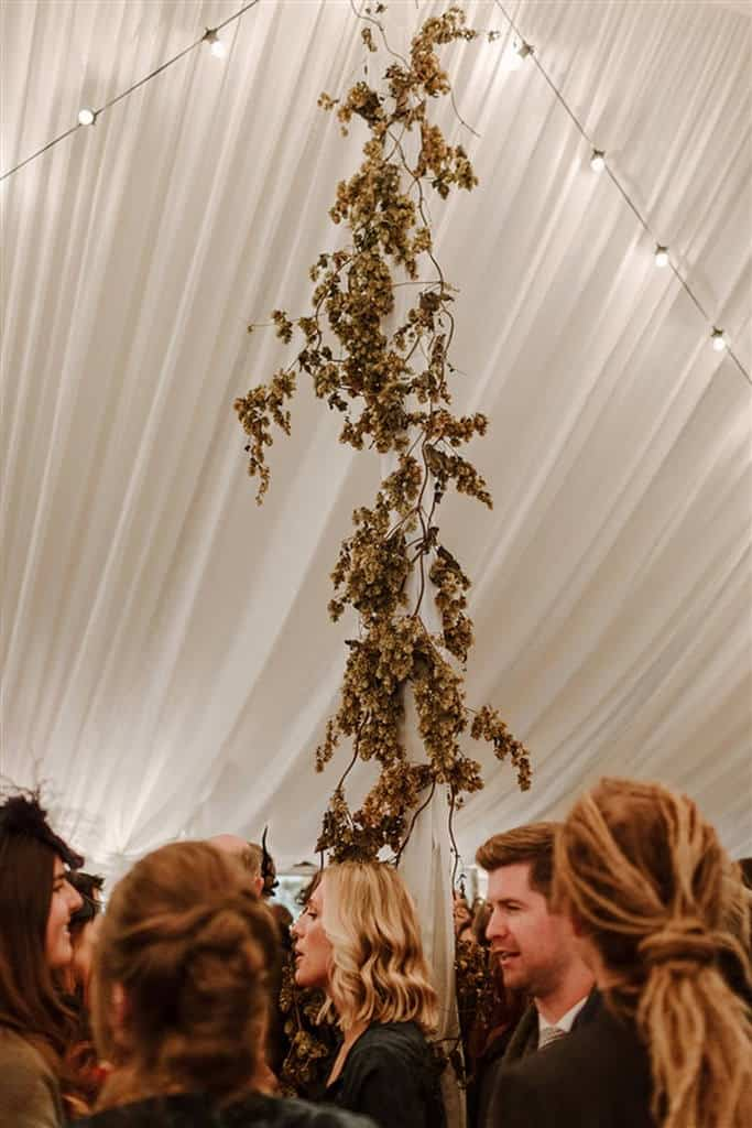 Floral decorated centerpoles in wedding marquee