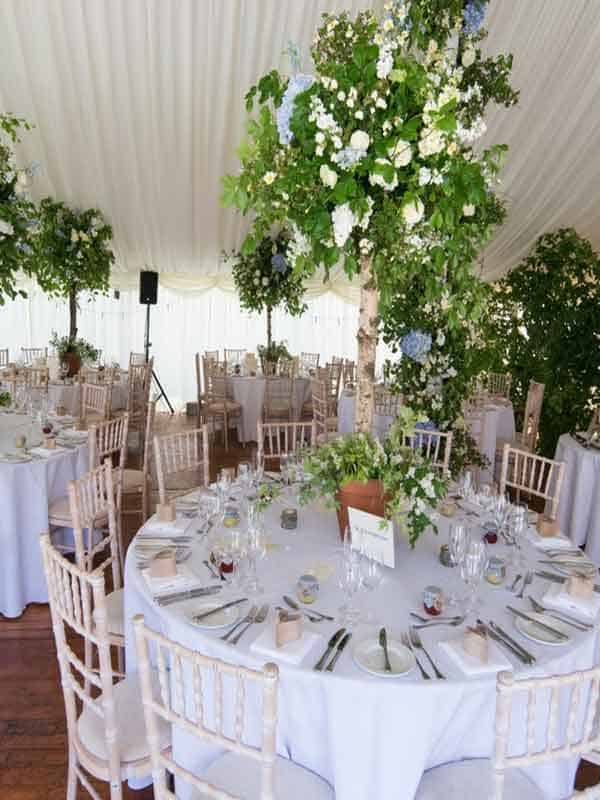 Interior of wedding marquee Edinburgh with tables and chairs and floral decorations