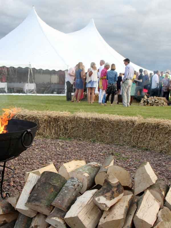 friends gather outside a marquee hire Scotland for a BBQ