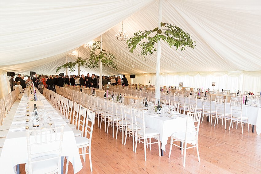 Interior of new century wedding marquee with tables and chairs in rows and wooden floor