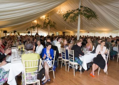 wedding guests eating at tables in a wedding marquee hire