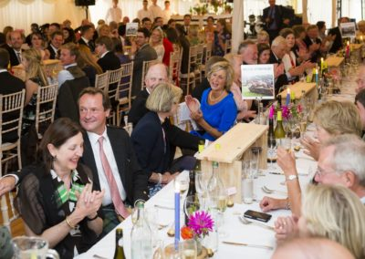 Guests sitting at tables enjoying the speaches in a new century marquee hire