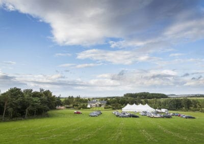 wedding marquee hire in field surrounded by guests cars