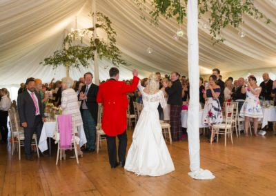 the bride and groom arrive into the wedding marquee hire and the guests are waiting to welcome them