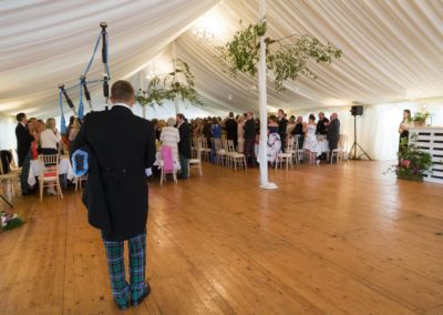 The wedding piper playing bagpipes inside a wedding marquee hire in Scotland