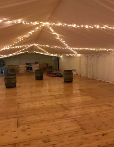 Whiskey barrels in a wedding marquee hire used as drinks tables