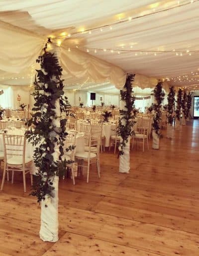 Centrepoles decorated with flowers in a wedding marquee hire in East Lothian