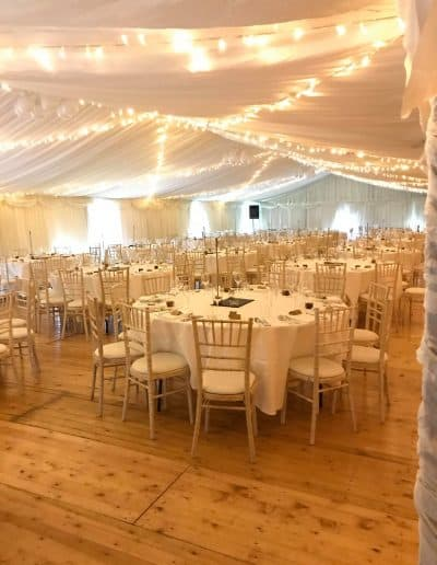 marquee lighting above tables in a wedding marquee hire on a farm