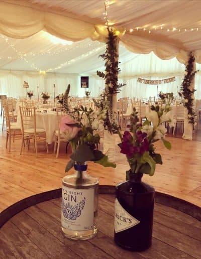 Gin bottles flower vases in a wedding marquee hire