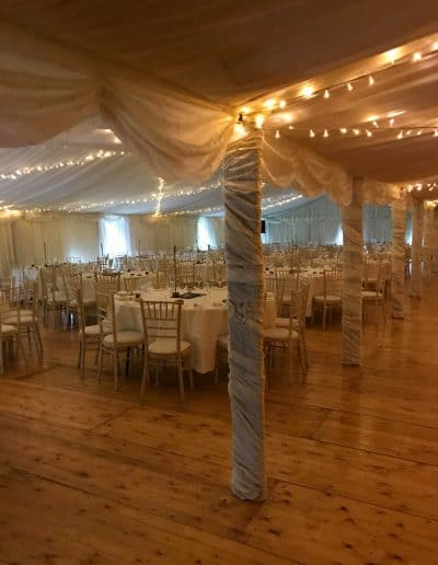 Tables and decorated poles on a wedding marquee hire in Scotland